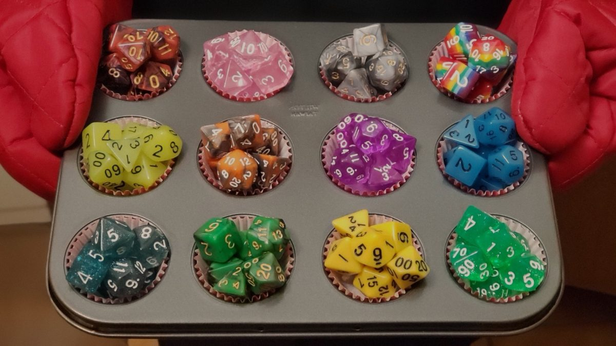Holding a cupcake pan filled with colorful dice.